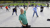 In this Oct. 2, 2019, photo, Whitey Christian performs tai chi at the Salt Lake Main Library, in Salt Lake City. The participants are homeless people who take part in a free tai chi program run by a retired couple who started the classes three years earlier. Now, more than 50 people regularly attend. (AP Photo/Rick Bowmer)