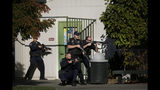 Santa Rosa police officers hold guns as they search the campus of Ridgway High School for suspects after a shooting at the school in Santa Rosa, Calif., Tuesday, Oct. 22, 2019. (Beth Schlanker/The Press Democrat via AP)
