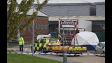 Police officers attend the scene after a truck, seen in rear, was found to contain a large number of dead bodies, in Thurrock, South England, early Wednesday Oct. 23, 2019. Police in southeastern England said that 39 people were found dead Wednesday inside the truck container believed to have come from Bulgaria. (Stefan Rousseau/PA via AP)