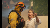 A Palisades resident talks with a firefighter before evacuating her home as a wildfire erupts in the Pacific Palisades area of Los Angeles, Monday, Oct. 21, 2019. (AP Photo/Christian Monterrosa)
