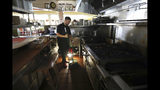FILE - In this Oct. 10, 2019, file photo, Salvador Espinosa sweeps in the kitchen of a Mary's Pizza Shack restaurant during a Pacific Gas and Electric Co. power shutdown in Santa Rosa, Calif. Authorities say power outages have started Wednesday, Oct. 23, 2019, in Northern California after the state's largest utility said it was planning a widespread blackout citing wildfire danger. The Santa Rosa Fire Department tweeted Wednesday that shutoffs had started in the city and it was getting multiple reports of outages. Pacific Gas & Electric said earlier Wednesday it was going forward with blackouts later in the day that could affect 450,000 people in 17 counties of Northern California. (Christopher Chung/The Press Democrat via AP, File)/The Press Democrat via AP)