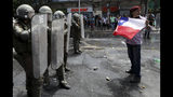 A demonstrator holds a Chilean flag in front of a line of police in riot gear during a protest in Santiago, Chile, Wednesday, Oct. 23, 2019. Rioting, arson attacks and violent clashes wracked Chile as the government raised the death toll to 15 in an upheaval that has almost paralyzed the South American country long seen as the region's oasis of stability. (AP Photo/Rodrigo Abd)