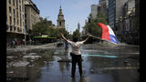 A demonstrator holds a Chilean flag during a protest in Santiago, Chile, Wednesday, Oct. 23, 2019. Rioting, arson attacks and violent clashes wracked Chile as the government raised the death toll to 15 in an upheaval that has almost paralyzed the South American country long seen as the region's oasis of stability. (AP Photo/Rodrigo Abd)
