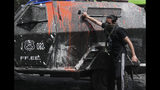 A demonstrator walks up to a police armored vehicle during clashes in Santiago, Chile, Wednesday, Oct. 23, 2019. Rioting, arson attacks and violent clashes wracked Chile as the government raised the death toll to 15 in an upheaval that has almost paralyzed the South American country long seen as the region's oasis of stability. (AP Photo/Rodrigo Abd)