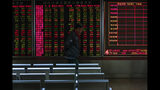 An investor walks by an electronic screen displaying stock prices at a brokerage house in Beijing, Wednesday, Oct. 23, 2019. Asian stock markets followed Wall Street lower Wednesday after major companies reported mixed earnings and an EU leader said he would recommend the trade bloc allow Britain to delay its departure. (AP Photo/Andy Wong)