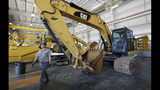 In this Sept. 18, 2019, photo a Puckett Machinery Company technician walks past a new heavy duty Caterpillar excavator that awaits modification at Puckett Machinery Company in Flowood, Miss. Caterpillar Inc. reports financial earns on Wednesday, Oct. 23. (AP Photo/Rogelio V. Solis)