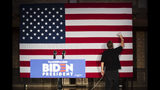 A worker smooths the surface of a United States flag ahead of a campaign event for Democratic presidential candidate former Vice President Joe Biden, Wednesday, Oct. 23, 2019, in Scranton, Pa. (AP Photo/Matt Rourke)