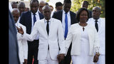 President Jovenel Moïse, left, holds hands with his wife Martine after laying flowers to mark the anniversary of the death of Haitian revolution leader Jean-Jacques Dessalines, in Champ de Mars, adjacent to the National Palace, in Port-au-Prince, Haiti, Thursday Oct. 17, 2019. Haiti's embattled president was forced on Thursday to hold a private ceremony amid heavy security for what is usually a public celebration of one of the country's founding fathers. (AP Photo/Rebecca Blackwell)