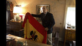 Spanish dictator General Francisco Franco's grandson, Francisco Franco Martinez-Bordiu holds up a pre-constitutional Spanish flag he wants draped over the coffin General Franco during his reburial Thursday after an interview with The Associated Press in Madrid, Spain, Wednesday, Oct. 23, 2019. Weather permitting, the Spanish dictator's preserved body will be flown Thursday by helicopter to the Franco family's private chapel in the Mingorrubio cemetery. It's a discrete site compared to the Valley of the Fallen, a vainglorious mausoleum and basilica that Franco built and where he was buried in 1975. The complex, which is topped by a 152-meter (500-foot) granite cross that can be seen for miles, still remains a National Heritage site. (AP Photo/Paul White)