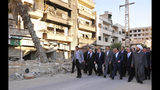 FILE - In this Sept. 12, 2016, file photo, released by the Syrian official news agency SANA, Syrian President Bashar Assad, center, walks on a street with officials after performing the morning Eid al-Adha prayers in Daraya, a blockaded Damascus suburb, Syria. Assad has snapped up a prize from world powers that have been maneuvering in his country's multifront wars. Without firing a shot, his forces are returning to towns and villages in northeastern Syria where they haven't set foot for years. (SANA via AP, File)