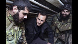 FILE - In this Dec. 31, 2014, file photo released by the Syrian official news agency SANA, Syrian President Bashar Assad, center, speaks with Syrian troops during his visit to the front line in the eastern Damascus district of Jobar, Syria. Assad has snapped up a prize from world powers that have been maneuvering in his country's multifront wars. Without firing a shot, his forces are returning to towns and villages in northeastern Syria where they haven't set foot for years. (SANA via AP, File)
