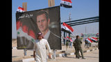 """FILE - In this Sept. 30, 2019, file photo, a man passes a poster of Syrian President Bashar Assad with Arabic that reads, """"Congratulations victory,"""" while crossing the border into Syria at the newly opened crossing between the Iraqi town of Qaim and Syria's Boukamal, Syria. Assad has snapped up a prize from world powers that have been maneuvering in his country's multifront wars. Without firing a shot, his forces are returning to towns and villages in northeastern Syria where they haven't set foot for years. (AP Photo/Hadi Mizban, File)"""