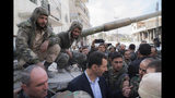 FILE - In this March 18, 2018, file photo released on the official Facebook page of the Syrian Presidency, Syrian President Bashar Assad, center, speaks with Syrian troops during his visit to the front line in the newly captured areas of eastern Ghouta, near the capital Damascus, Syria. Assad has snapped up a prize from world powers that have been maneuvering in his country's multifront wars. Without firing a shot, his forces are returning to towns and villages in northeastern Syria where they haven't set foot for years. (Syrian Presidency Facebook Page via AP, File)