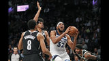 Brooklyn Nets guard Spencer Dinwiddie (8) and center Jarrett Allen, center, defend against Minnesota Timberwolves center Karl-Anthony Towns (32) as Towns goes up for a layup during the first half of an NBA basketball game Wednesday, Oct. 23, 2019, in New York. (AP Photo/Kathy Willens)