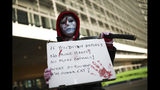 A masked man holds a placard and a fake sword during a small protest by Extinction Rebellion climate change activists outside the European Commission headquarters in Brussels, Thursday, Oct. 31, 2019. (AP Photo/Francisco Seco)