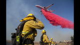 Firefighters brace themselves for incoming fire retardant during the Easy Fire, Wednesday, Oct. 30, 2019, in Simi Valley, Calif. Fire officials say they're investigating the cause of the fire. (AP Photo/Christian Monterrosa)