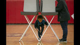 Declan Brady peeks under the voting booth while his grandmother Darlene Walker votes at Drew Middle School on Election Day in Stafford, Va., Tuesday, Nov. 5, 2019. (Mike Morones/The Free Lance-Star via AP)