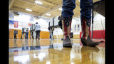 Chief Election Official Sandy Pace wears her patriotic-themed boots while staffing the polling station at Drew Middle School on Election Day in Stafford, Va., Tuesday, Nov. 5, 2019. (Mike Morones/The Free Lance-Star via AP)