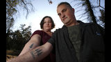 In this Thursday, Oct. 17, 2019, photo, Laura and Chris Smith display their Paradise tattoos they had done to show support for their former community during a visit to Paradise, Calif. The Smiths are now living in a small apartment in Chico where they say neighbors complain if they shut the door too hard. (AP Photo/Rich Pedroncelli)