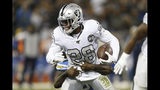 Oakland Raiders running back Josh Jacobs (28) tries to get away from Los Angeles Chargers defensive end Melvin Ingram III during the first half of an NFL football game in Oakland, Calif., Thursday, Nov. 7, 2019. (AP Photo/D. Ross Cameron)