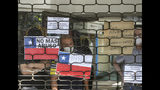 People look out from a shuttered mall at anti-government protests in Santiago, Chile, Wednesday, Nov. 6, 2019. Chile's president Sebastian Pinera announced he is sending a bill to Congress that would raise the minimum salary, one of a series of measures to try to contain nearly three weeks of anti-government protests. (AP Photo/Esteban Felix)