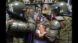 A woman is detained by the police during an anti-government protest in Santiago, Chile, Wednesday, Nov. 6, 2019. Chile's president Sebastian Pinera announced he is sending a bill to Congress that would raise the minimum salary, one of a series of measures to try to contain nearly three weeks of anti-government protests. (AP Photo/Esteban Felix)