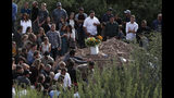 Family and friends gather for the burial service for Dawna Ray Langford, 43, and her sons Trevor, 11, and Rogan, 2, who were killed in an ambush earlier this week, at a small cemetery in La Mora, Mexico, Thursday, Nov. 7, 2019. As Mexican soldiers stood guard, the three were laid to rest in a single grave at the first funeral for the victims of a drug cartel ambush that left nine American women and children dead. (AP Photo/Marco Ugarte)