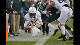 Penn State quarterback Sean Clifford, left, dives for a first down against Michigan State's Shakur Brown (29) during the first quarter of an NCAA college football game, Saturday, Oct. 26, 2019, in East Lansing, Mich. (AP Photo/Al Goldis)