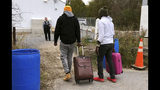 In this Nov. 4, 2019, photo, two men from Nigeria illegally cross the U.S. border at Roxham Road in Champlain, N.Y., into Canada where Royal Canadian Mounted Police stand, rear, in Saint-Bernard-de-Lacolle, Quebec. Since early 2017, when people who despaired of finding a permanent safe haven in the United States began turning to Canada for help, around 50,000 people have illegally entered Canada, many through Roxham Road in upstate New York. A case being heard in a Toronto court this week could end the use of Roxham Road. (AP Photo/Wilson Ring)