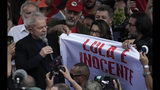 "Brazil's former President Luiz Inacio Lula da Silva holds the corner of a banner that reads in Portuguese ""Lula is innocent"" as he speaks to supporters outside the Federal Police headquarters where he was imprisoned on corruption charges in Curitiba, Brazil, Friday, Nov. 8, 2019. Da Silva walked out of the prison Friday, less than a day after the Supreme Court ruled that a person can be imprisoned only after all the appeals have been exhausted. (AP Photo/Leo Correa)"