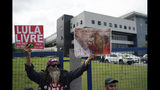 """A supporter of Brazil's former President Luiz Inacio Lula da Silva holds up signs that reads in Portuguese """"Free Lula,"""" left, and """"Women for Lula free."""" outside the Federal Police headquarters where the former leader is imprisoned in Curitiba, Brazil, Friday, Nov. 8, 2019. Da Silva's lawyers have begun legal procedures requesting his release from prison, following a Supreme Court decision late Thursday that a person can be imprisoned only after all appeals to higher courts have been exhausted. Da Silva has been detained since April 2018 after being convicted of corruption. (AP Photo/Leo Correa)"""