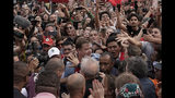 Brazil's former President Luiz Inacio Lula da Silva, bottom, back to camera, waves to supporters as he exits the the Federal Police headquarters where he was imprisoned on corruption charges in Curitiba, Brazil, Friday, Nov. 8, 2019. Da Silva walked out of a Curitiba prison Friday, less than a day after the Supreme Court ruled that a person can be imprisoned only after all the appeals have been exhausted. (AP Photo/Leo Correa)