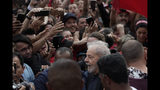 Brazil's former President Luiz Inacio Lula da Silva, bottom, is surrounded by supporters as he exits the Federal Police headquarters where he was imprisoned on corruption charges in Curitiba, Brazil, Friday, Nov. 8, 2019. Da Silva walked out of a Curitiba prison Friday, less than a day after the Supreme Court ruled that a person can be imprisoned only after all the appeals have been exhausted. (AP Photo/Leo Correa)