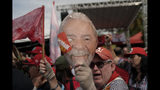 A supporter of Brazil's former President Luiz Inacio Lula da Silva holds up a mask of Da Silva outside the Federal Police headquarters where the former leader is imprisoned in Curitiba, Brazil, Friday, Nov. 8, 2019. Da Silva's lawyers have begun legal procedures requesting his release from prison, following a Supreme Court decision late Thursday that a person can be imprisoned only after all appeals to higher courts have been exhausted. Da Silva has been detained since April 2018 after being convicted of corruption. (AP Photo/Leo Correa)