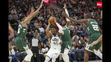 Utah Jazz guard Donovan Mitchell (45) drives to the basket as Milwaukee Bucks' Wesley Matthews (9), Giannis Antetokounmpo (34) and Khris Middleton (22) defend during the first half of an NBA basketball game Friday, Nov. 8, 2019, in Salt Lake City. (AP Photo/Rick Bowmer)