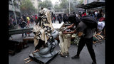 An anti-government protester beheads a statue of Jesus Christ that was taken from a church to be added to a barricade, in Santiago, Chile, Friday, Nov. 8, 2019. Chile's president on Thursday announced measures to increase security and toughen sanctions for vandalism following three weeks of protests that have left at least 20 dead. (AP Photo/Esteban Felix)