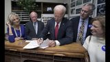 Democratic presidential candidate former Vice President Joe Biden files to have his name listed on the New Hampshire primary ballot, Friday, Nov. 8, 2019, in Concord, N.H. At left is his wife Jill Biden, and New Hampshire Secretary of State Bill Gardner. (AP Photo/Charles Krupa)