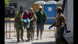 U.S. soldiers carry an elderly Haitian woman to see a U.S. military doctor from the US Navy hospital ship USNS Comfort anchored off Port-au-Prince, Haiti, Friday, Nov. 8, 2019. The visit of the hospital ship comes as violent demonstrations and street barricades have led several hospitals across the country to run out of medical supplies and some have temporarily closed as protesters keep demanding the president's resignation. (AP Photo/Dieu Nalio Chery)