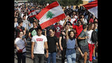Student protesters wave their national flags and shout slogans, as they protest against the government in front of the education ministry in Beirut, Lebanon, Friday, Nov. 8, 2019. Lebanese protesters are rallying outside state institutions and ministries to keep up the pressure on officials to form a new government to deal with the country's economic crisis. (AP Photo/Hussein Malla)