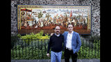 Federico Acosta, a Mexican who traces his lineage back 16 generations back to Moctezuma's daughter, left, and Italian Ascanio Pignatelli also of the 16th generation descended from Hernan Cortes' daughter, pose for a photo in front of a mural commemorating the meeting of the Spanish conquistador and the Aztec emperor, in Mexico City, Friday, Nov. 8, 2019. Descendants are meeting in Mexico City to mark the 500th anniversary of their forbearers' first encounter. (AP Photo/Eduardo Verdugo)