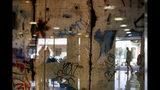 En esta imagen, tomada el 26 de septiembre de 2019, la silueta de un hombre se refleja en un cristal que protege un fragmento del Muro de Berlín en la Editorial Perfil, en Buenos Aires, Argentina. (AP Foto/Natacha Pisarenko)