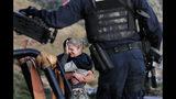 En esta imagen, tomada el 6 de noviembre de 2019, custodiados por las fuerzas de seguridad mexicanas, miembros de la familia LeBarón lloran a sus muertos en el lugar donde nueve ciudadanos estadounidenses _ tres mujeres y seis niños _ fueron asesinados en una emboscada de un cártel, cerca de Bavispe, en la frontera entre los estados de Sonora y Chihuahua, México. (AP Foto/Marco Ugarte)