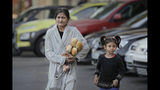 FILE- In this Sunday, Oct. 27, 2019 file picture a woman clutching loafs of bread and some eggs walks along with a child by a cleaning facility during a visit to a poor area of the Romanian capital by Romanian caretaker Prime Minister and presidential candidate supported by the ruling Social Democratic party (PSD) Viorica Dancila in Bucharest, Romania. Romania will hold presidential elections on Nov. 10. (AP Photo/Vadim Ghirda, File)