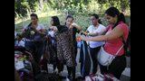 Fotografía del 3 de noviembre de 2019 de mujeres viendo ropa usada en un mercado de segunda mano en Caracas, Venezuela. Algunos de estos mercados surgen los domingos o se organizan a través de redes sociales. Los vendedores sacan dinero vendiendo sus posesiones como ropa o artículos del hogar para pagar por una nueva vida en el extranjero. (AP Foto/Ariana Cubillos)