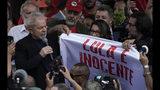 """El expresidente de Brasil Luiz Inácio Lula da Silva, sostiene la esquina de una pancarta con la frase (en portugués) """"Lula es inocente"""" mientras se dirige a sus seguidores en el exterior de la sede de la Policía Federal, donde pasó meses encarcelado por cargos de corrupción, en Curitiba, Brasil, el 8 de noviembre de 2019. (AP Foto/Leo Correa)"""