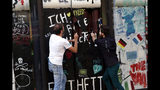 El chocolatero francés Patrick Roger, izquierda, y su asistente creativo Angelo Dao destruyen una réplica hecha de chocolate del Muro de Berlín para celebrar el 30 aniversario de la caída de la barrera en París, el sábado 9 de noviembre de 2019. (AP Foto/Thibault Camus)