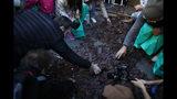 Personas recogen los trozos de una réplica hecha de chocolate del Muro de Berlín en París, el sábado 9 de noviembre de 2019. (AP Foto/Thibault Camus)