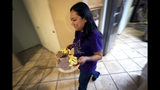 Karina Ruiz serves dinner at her home, Thursday, Nov. 7, 2019 in Glendale, Ariz. Karina is in a program dating back to the Obama administration that allows immigrants brought here as children to work and protects them from deportation. The U.S. Supreme Court will hear arguments Tuesday, Nov. 12, about President Donald Trump's attempt to end the program, and the stakes are particularly high for the older generation of people enrolled in Deferred Action for Childhood Arrivals, known as DACA. (AP Photo/Matt York)