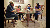 From left; Humberto Diaz, John Diaz, 7, Joseph Diaz, 10, right, and Karina Ruiz eat dinner at their home, Thursday, Nov. 7, 2019 in Glendale, Ariz. Karina is in a program dating back to the Obama administration that allows immigrants brought here as children to work and protects them from deportation. The U.S. Supreme Court will hear arguments Tuesday, Nov. 12, about President Donald Trump's attempt to end the program, and the stakes are particularly high for the older generation of people enrolled in Deferred Action for Childhood Arrivals, known as DACA. (AP Photo/Matt York)