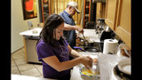 Karina Ruiz and Humberto Diaz prepare dinner at their home, Thursday, Nov. 7, 2019 in Glendale, Ariz. Karina is in a program dating back to the Obama administration that allows immigrants brought here as children to work and protects them from deportation. The U.S. Supreme Court will hear arguments Tuesday, Nov. 12, about President Donald Trump's attempt to end the program, and the stakes are particularly high for the older generation of people enrolled in Deferred Action for Childhood Arrivals, known as DACA. (AP Photo/Matt York)